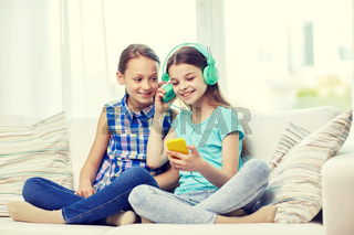 happy girls with smartphone and headphones