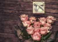 Pink roses over blank paper with gift box
