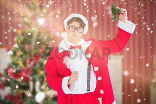 Composite image of geeky hipster in santa costume holding mistletoe