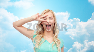 smiling young woman or teenage girl showing peace