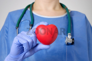 Red heart in the hand of a doctor