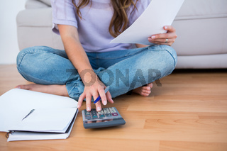 Woman calculating receipts lying on the floor