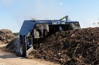 Kompost wird mit Kompostwender bearbeitet und Kompostierung beschleunigt