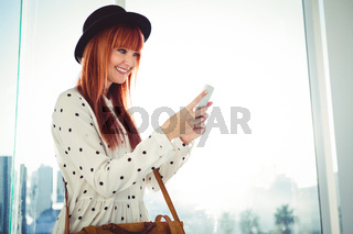 Smiling hipster woman texting with her smartphone