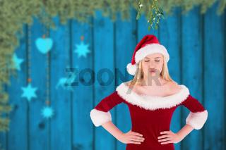 Composite image of festive cute blonde under mistletoe