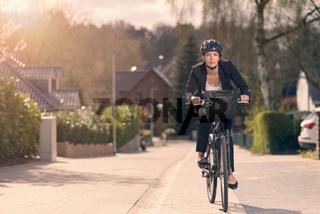 Junge Geschäftsfrau fährt mit dem Fahrrad