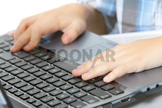 boy's hand typing on laptop keyboard