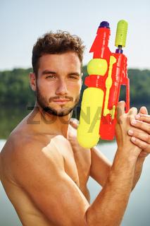 Mann mit Wasserpistole steht stolz am See