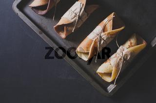 Rustic breakfast with chocolate pancakes on blackboard, flat lay