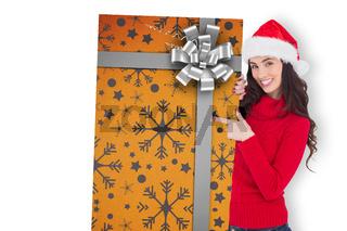 Composite image of smiling brunette in santa hat pointing gift card