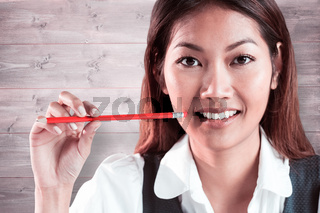 Composite image of smiling businesswoman holding a pencil