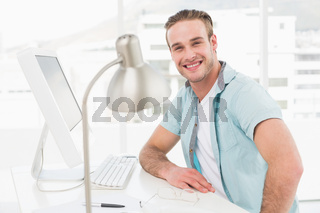Smiling casual businessman sitting at desk
