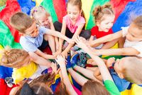 Close view of group of kids with their hands one on another