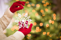 Woman Wearing Seasonal Red Mittens Holding White Snowflake Christmas Ornament