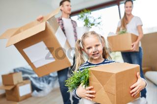 Mädchen und Eltern tragen Umzugskarton