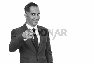 Mature happy Persian businessman pointing finger at camera