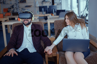 Adult bearded man with virtual reality vr glasses with co-worker at office