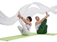 Couple doing yoga exercise in studio isolated shot