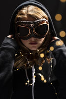 Lovely Blonde Teenage Model A Jacket and Goggles Against A Black Background With Lights Around Her