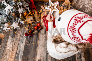 Female holds a Christmas star sitting by the tree