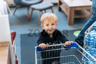 A little boy and a big cart in the supermarket