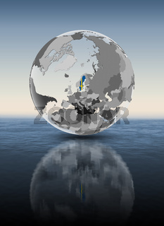 Sweden on translucent globe above water