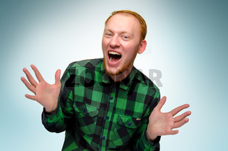 portrait of red haired happy man show his hands. caucasian male teenager maked surprise. redhead guy scream and laughs. reaction to surprise is overjoyed shock. emotion is glad. confident, funny boy