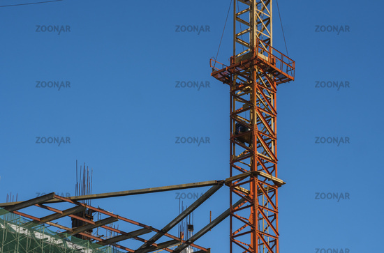 Crane and building construction site against blue sky. Metal construction of unfinished building on construction. Tower Crane use for building of multi storage building.