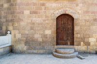 External vaulted closed decorated wooden grunge door in bricks stone wall