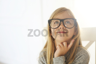 Smiling cute little girl with black eyeglasses over white background.