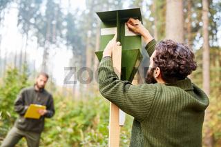 Praktikant und Förster kontrollieren Borkenkäferfalle