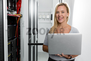 Technician examining server in server room with laptop