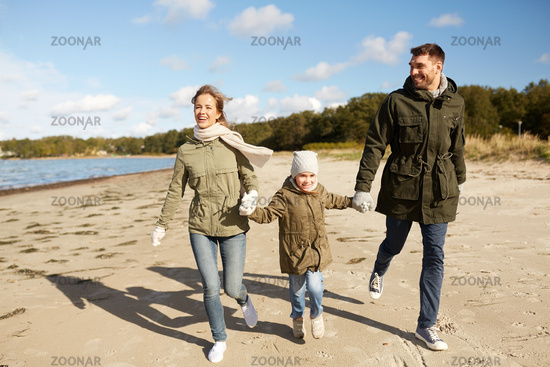 happy family running along autumn beach