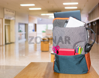 Heavily loaded backpack with school supplies in modern entrance hall