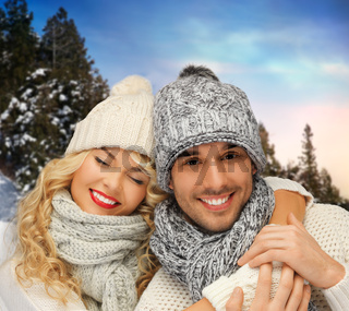 smiling couple in sweaters over winter background