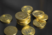 Stack of golden Ethereum bitcoin coin with a lot of bitcoins coins on a table. Virtual cryptocurrency concept. Mining of bitcoins online bussiness. Bitcoins trading.