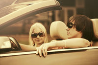 Happy young couple driving convertible car