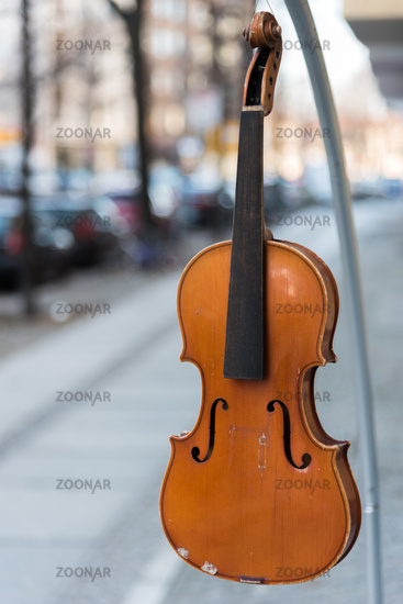 A violin without strings hangs on the hook