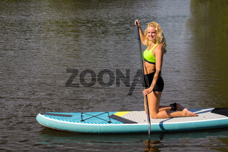 Young woman paddling with SUP on water