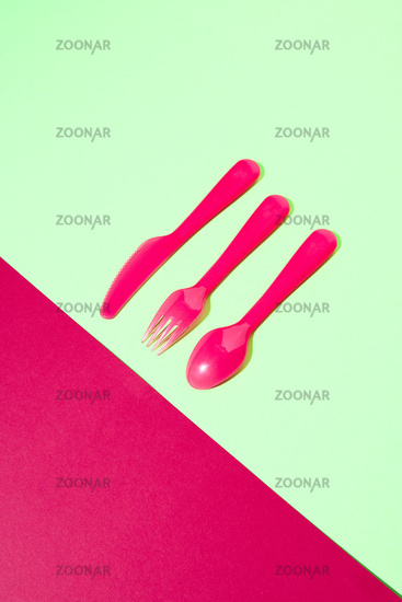 Dining set from colored plastic cutlery on a duotone background.