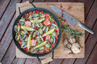 Seafood paella in a pan on a wooden table with a knife, garlic, mushrooms and herbs