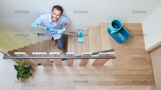 Hausmann mit Wischmopp beim putzen von Treppe