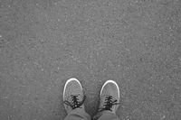 feet in canvas shoes standing on asphalt street