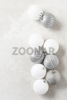 Silver and white Christmas Tree Balls on a light mottled gray surface. Vertical with copy space.