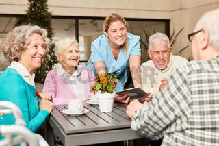 Senioren und Pflegekraft mit Tablet Computer