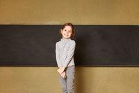 Glückliches Mädchen als Schülerin vor einer Tafel