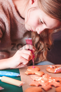Girl decorating baked Christmas gingerbread cookies with frosting