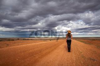Farm girl watching storm over the arid desert