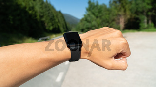 looking at smartwatch or sport watch, checking gps navigation position map or heart rate pulse trace. Sport and fitness outdoors in nature.
