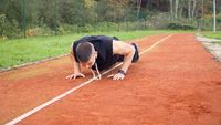 Young fit man doing push ups in the morning outdoor on the running race track